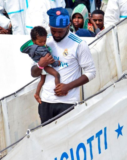 "(Orietta Scardino/ANSA via AP). A migrant man holds a baby as they disembark from Italian Coast Guard vessell ""Diciotti"" as it docks at the Sicilian port of Catania, southern Italy, Wednesday, June 13, 2018. The vessel docked in Catania with 932 migran..."