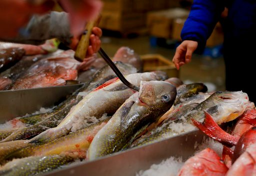 (AP Photo/Julie Jacobson). A fishmonger pulls tilefish for a buyer at the New Fulton Fish Market in New York on Monday, Jan. 8, 2018. The U.S. seafood industry is worth $17 billion a year, more than 90 percent of which is made up of imports.