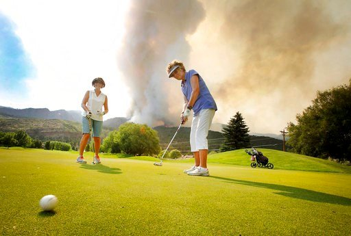 (Jerry McBride/The Durango Herald via AP). In this Tuesday, June 12, 2018, photograph, Sandy Elliott follows her putt while playing a round of golf with Marlene Gebhardt at Dalton Golf and Country Club with the 416 Fire burning behind them near Durango...