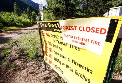 (Jerry McBride/The Durango Herald via AP). In this Tuesday, June 12, 2018, photograph, a sign is posted to show that there is no access because of wildfires to San Juan National Forest on County Road 124 north May Day near Durango, Colo..