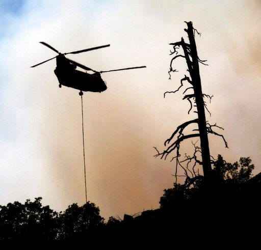 (Jerry McBride /The Durango Herald via AP). In this Tuesday, June 12, 2018, photo, smoke envelops a helicopter as it is used to battle a wildfire near Durango, Colo.