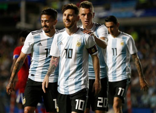 (AP Photo/Natacha Pisarenko). FILE - In this May 29, 2018 file photo Argentina's Manuel Lanzini, left, Giovanni Lo Celso, second right, and Angel Di Maria, right, congratulate teammate Lionel Messi, second left, after his hat trick during a friendly so...