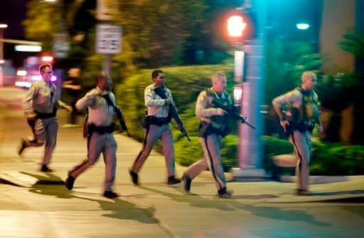 (AP Photo/John Locher, File). FILE - In this Oct. 1, 2017, file photo, police run toward the scene of a shooting near the Mandalay Bay resort and casino on the Las Vegas Strip in Las Vegas. Police planned to release body-worn camera video from officers...
