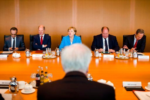 (AP Photo/Markus Schreiber). German Interior Minister Horst Seehofer, front, sits on the opposite of German German Chancellor Angela Merkel, center back ground, prior to the weekly cabinet meeting of the German government at the chancellery in Berlin, ...