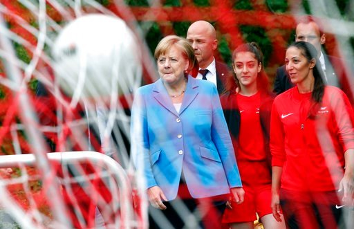 (AP Photo/Michael Sohn). A ball flounces in the goal's net as German Chancellor Angela Merkel, center avrrives for a girls soccer training session at a soccer club in Berlin, Germany, Wednesday, June 13, 2018.