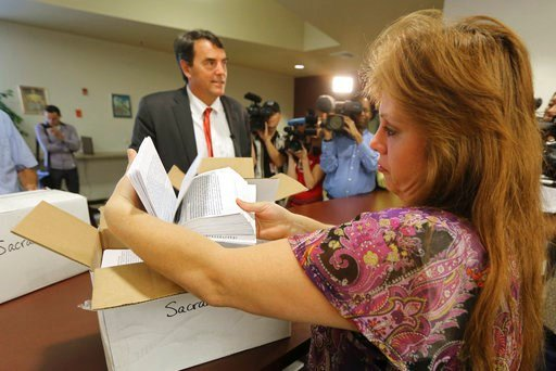 (AP Photo/Rich Pedroncelli, File). FILE - In this July 15, 2014 file photo, Heather Ditty, elections manager for the Sacramento County Registrar of Voters, makes a quick inspection of some of the petitions turned in by Silicon Valley venture capitalist...