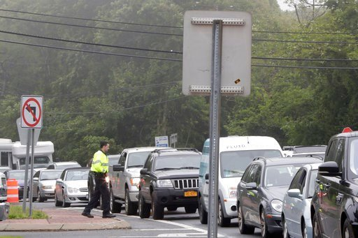 (AP Photo/Julio Cortez). A police officer stands near traffic along County Road 39 near the site of the U.S. Open Golf Championship, Wednesday, June 13, 2018, in Southampton, N.Y.