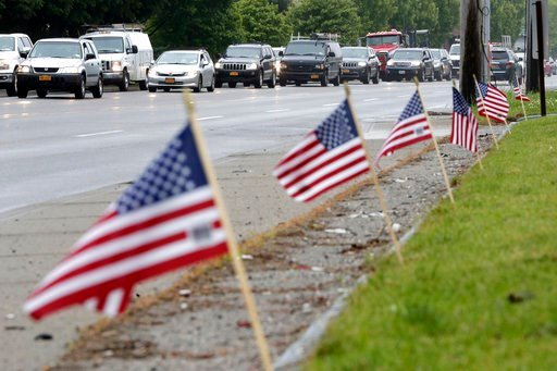 (AP Photo/Julio Cortez). Flags adorning the front of a gas station wave as vehicles stand in traffic along County Road 39 near the site of the U.S. Open Golf Championship, Wednesday, June 13, 2018, in Southampton, N.Y.