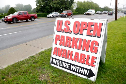 (AP Photo/Julio Cortez). A sign for parking is displayed in front of a private lot as vehicles drive slowly in traffic along County Road 39 near the site of the U.S. Open Golf Championship, Wednesday, June 13, 2018, in Southampton, N.Y.