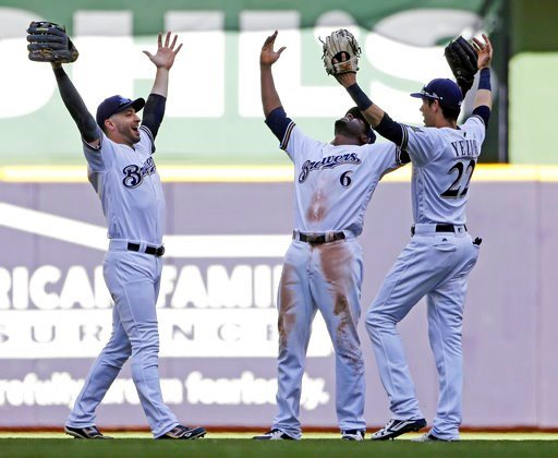 (AP Photo/Aaron Gash). Milwaukee Brewers, from left, Ryan Braun, Lorenzo Cain and Christian Yelich celebrate after a baseball game against the Chicago Cubs, Wednesday, June 13, 2018, in Milwaukee. The Brewers won 1-0.