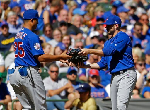 (AP Photo/Aaron Gash). Chicago Cubs' Brian Duensing, right, exchanges gloves with Will Venable after being called in from playing the left field position to pitch during the eighth inning of a baseball game against the Milwaukee Brewers Wednesday, June...