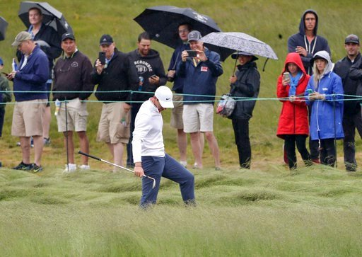 (AP Photo/Frank Franklin II). Rory McIlroy, of Northern Ireland, checks his lie in the fescue during a practice round for the U.S. Open Golf Championship, Wednesday, June 13, 2018, in Southampton, N.Y.