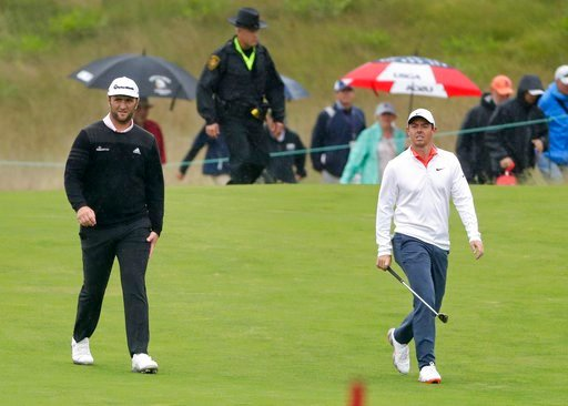 (AP Photo/Frank Franklin II). Jon Rahm, of Spain, left, walks with Rory McIlroy, of Northern Ireland, during a practice round for the U.S. Open Golf Championship, Wednesday, June 13, 2018, in Southampton, N.Y.