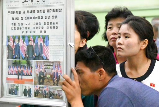 (Minoru Iwasaki/Kyodo News via AP). People look at the display of local newspaper reporting the meeting between North Korean leader Kim Jong Un and U.S. President Donald Trump, at a subway station in Pyongyang, North Korea Wednesday, June 13, 2018. The...