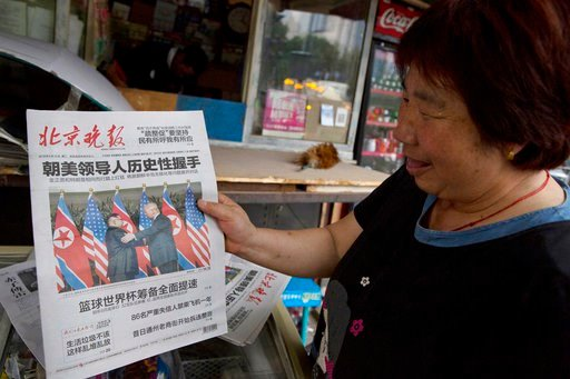 (AP Photo/Ng Han Guan). A newspaper vendor holds up a front page photo of the meeting in Singapore between U.S. President Donald Trump and North Korean leader Kim Jong Un at a newsstand in Beijing, China, Tuesday, June 12, 2018. China has suggested tha...