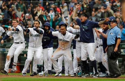(AP Photo/Ted S. Warren). Seattle Mariners. including Jean Segura, center, who scored the game-winning run on a two-run walk-off home run by Mitch Haniger, wait for Haniger at the plate during the ninth inning of a baseball game against the Los Angeles...