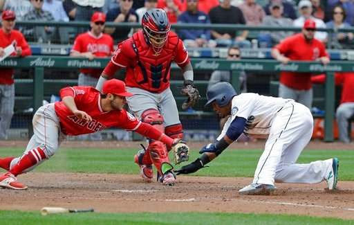 (AP Photo/Ted S. Warren). Los Angeles Angels third baseman David Fletcher, left, tags out Seattle Mariners' Jean Segura at the plate as catcher Martin Maldonado watches during the seventh inning of a baseball game Wednesday, June 13, 2018, in Seattle. ...