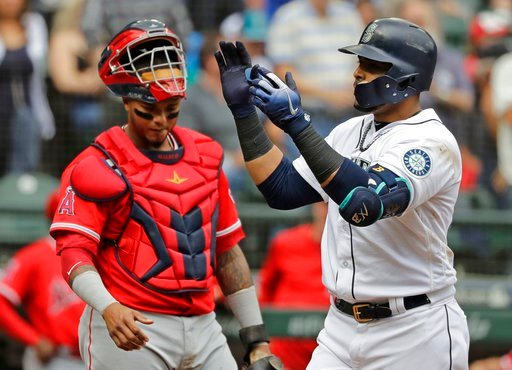 (AP Photo/Ted S. Warren). Seattle Mariners' Nelson Cruz, right, reacts as he crosses home plate next to Los Angeles Angels catcher Martin Maldonado after Cruz hit a two-run home run during the third inning of a baseball game, Wednesday, June 13, 2018, ...