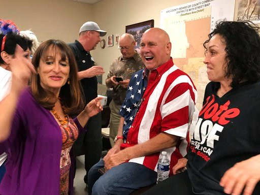 (David Montero /Los Angeles Times via AP). ADDS IDENITY OF WOMAN AT RIGHT AS HEIDI FLEISS -  In this Tuesday, June 12, 2018 photo Nevada brothel owner Dennis Hof, second from right celebrates after winning the primary election in Pahrump, Nev. Hof, the...