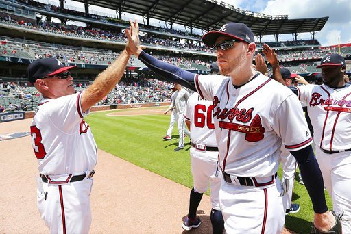 (Curtis ComptonAtlanta Journal-Constitution via AP). Atlanta Braves' Freedie Freeman, right foreground, gets a high five from manager Brian Snitker after the Braves defeated the New York Mets 2-0 in a baseball game in Atlanta, Wednesday, June 13, 2018.