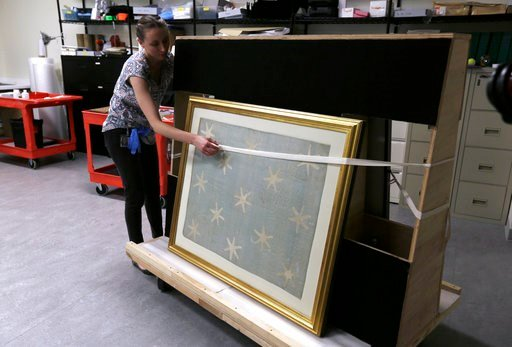 (AP Photo/Jacqueline Larma). Collections manager Michelle Moskal secures the Commander-in-Chief's Standard, Wednesday, June 13, 2018, before moving it to an exhibition gallery at the Museum of the American Revolution in Philadelphia. The faded and frag...