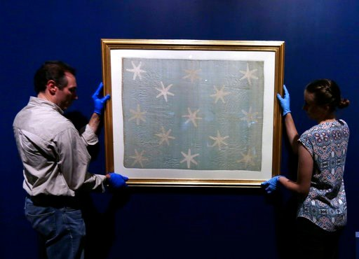 (AP Photo/Jacqueline Larma). Collections manager Michelle Moskal, right, and curator Mark Turdo hang the Commander-in-Chief's Standard, Wednesday, June 13, 2018, at an exhibition gallery in the Museum of the American Revolution in Philadelphia. The fad...