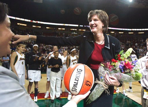 (AP Photo/Elaine Thompson, File). FILE - In this Aug. 19, 2005, file photo, Seattle Storm coach Anne Donovan, right, smiles as she is handed the game ball by team official Karen Bryant following the Storm's victory over the Minnesota Lyn  in Seattle. T...