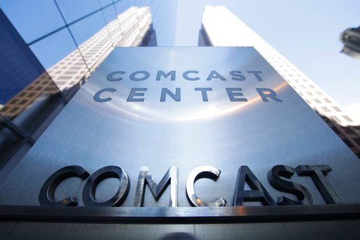(AP Photo/Matt Rourke, File). FILE - This March 29, 2017, file photo shows a sign outside the Comcast Center in Philadelphia. Comcast made a $65 billion bid Wednesday for Fox's entertainment businesses, setting up a battle with Disney to become the nex...