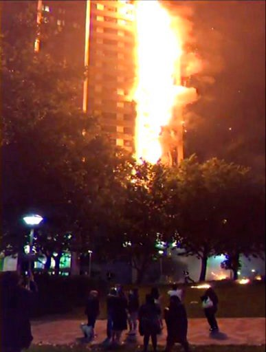 (Grenfell Tower Inquiry via AP, File). FILE - A June 14, 2017 handout grab taken from video issued by the Grenfell Tower Inquiry, timestamped at 01.26, shows the fire spreading up the tower. In 2017, the residential high-rise was destroyed by a fire th...