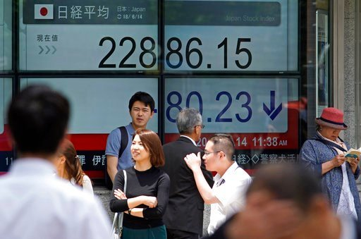 (AP Photo/Shuji Kajiyama). People walk by an electronic stock board of a securities firm in Tokyo, Thursday, June 14, 2018. Asian stock markets slumped on Thursday with South Koreans stocks plunging 1.6 percent on the first day of trading after an unpr...