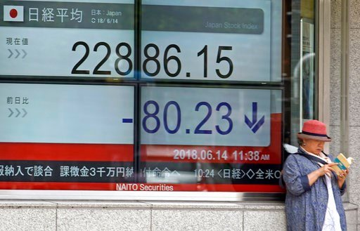 (AP Photo/Shuji Kajiyama). A woman reads a book in front of an electronic stock board showing Nikkei's stock index in Tokyo, Thursday, June 14, 2018. Asian stock markets slumped on Thursday with South Koreans stocks plunging 1.6 percent on the first da...