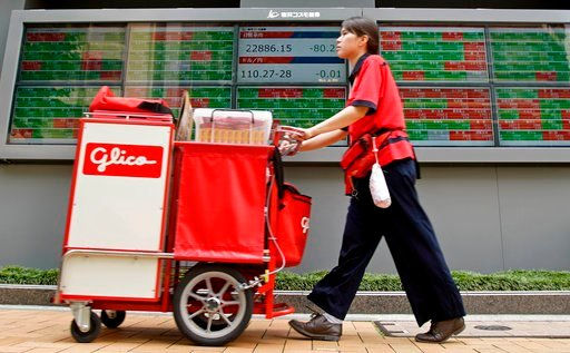 (AP Photo/Shuji Kajiyama). A drink vendor moves past an electronic stock board of a securities firm in Tokyo, Thursday, June 14, 2018. Asian stock markets slumped on Thursday with South Koreans stocks plunging 1.6 percent on the first day of trading af...