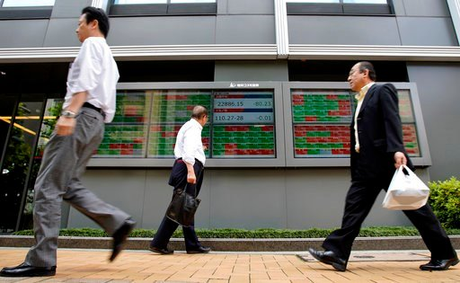 (AP Photo/Shuji Kajiyama). People walk past an electronic stock board of a securities firm in Tokyo, Thursday, June 14, 2018. Asian stock markets slumped on Thursday with South Koreans stocks plunging 1.6 percent on the first day of trading after an un...