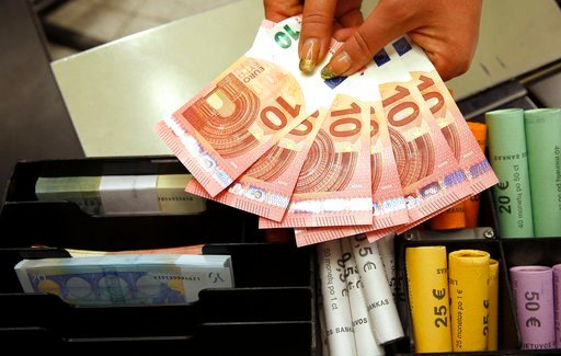 (AP Photo/Mindaugas Kulbis, File). FILE - In this Thursday, Jan. 1, 2015 file photo, euro coins and banknotes are shown by a salesclerk at a shop in Vilnius, Lithuania. Italy's economy minister says the new populist government isn't discussing any prop...