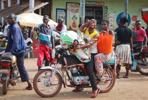 (AP Photo/Sam Mednick). In this photo taken Saturday, June 2, 2018, a motorcycle taxi driver carries a passenger through the streets of Mbandaka, Congo. Hundreds are being vaccinated in Congo's deadly Ebola outbreak, but busy taxi drivers who might be ...