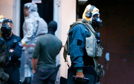 (David Young/dpa via AP). In this Tuesday June 12, 2018 photo, German police officers in protective gear leave an apartment building during an operation in Cologne, Germany. German police are searching the apartment of a 29-year-old Tunisian man who is...