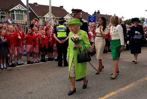 (Peter Byrne/Pool via AP). Britain's Queen Elizabeth II and Meghan, the Duchess of Sussex, third right, are welcomed by well-wishers after arriving by Royal Train at Runcorn Station, north west England, Thursday June 14, 2018.