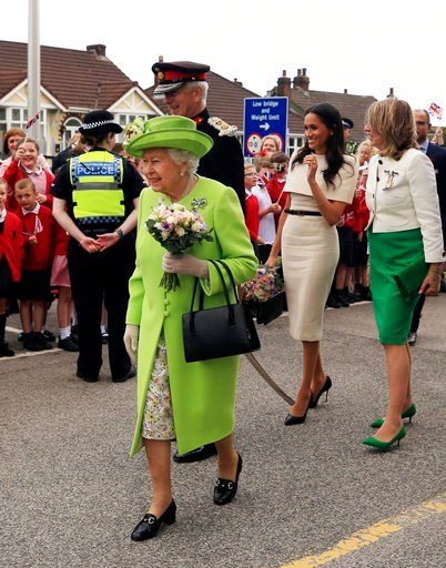 (Peter Byrne/Pool via AP). Britain's Queen Elizabeth II and Meghan, the Duchess of Sussex, second right, are welcomed by well-wishers after arriving by Royal Train at Runcorn Station, north west England, Thursday June 14, 2018.