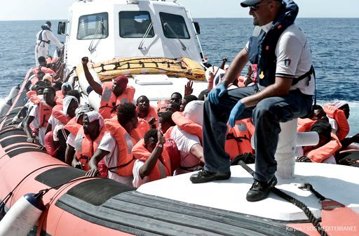 "(Kenny Karpov/SOS Mediterranee via AP). This June 12, 2018 photo released Wednesday, June 13, 2018 by French NGO ""SOS Mediterranee"" shows migrants waving after being transferred from the Aquarius ship to Italian Coast Guard boats, in the Mediterranean ..."