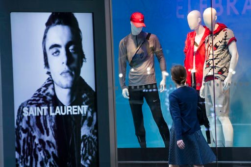(AP Photo/Mary Altaffer, File). FILE- In this June 6, 2018, photo, an advertisement for Saint Laurent is seen on a bus stop display as a pedestrian walks past a window display at the Lord & Taylor flagship store on Fifth Avenue in New York. On Thur...