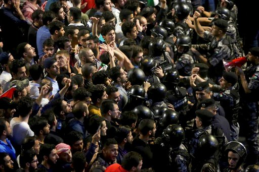 (AP Photo/Raad al-Adayleh, File). FILE - In this June 7, 2018 file photo, Jordanian riot police and security forces scuffle with protesters during a demonstration outside the Prime Minister's office in Amman. Jordan's new prime minister, Omar Razzaz, w...