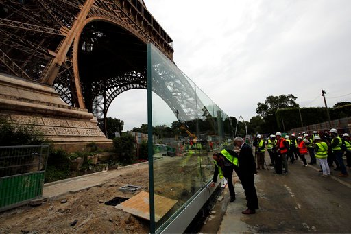 (AP Photo/Francois Mori). Bernard Gaudillere, president of the SETE, Eiffel Tower Exploitation Society, second left, stands in front of a new security bulletproof glass barrier under construction around the Eiffel Tower in Paris, France, Thursday, June...