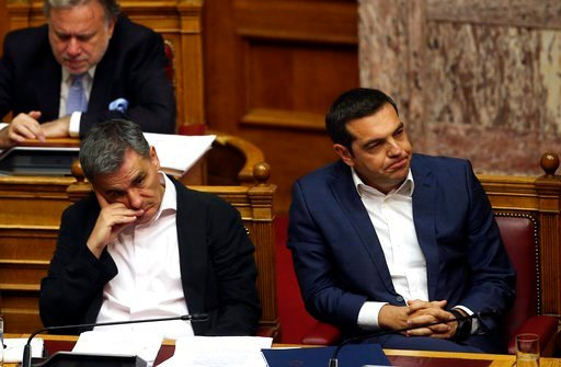 (AP Photo/Petros Giannakouris). Greek Prime Minister Alexis Tsipras, right, and Finance Minister Euclid Tsakalotos attend a parliamentary session in Athens, on Thursday, June 14, 2018. The head of Greece's main opposition party Kyriakos Mitsotakis subm...