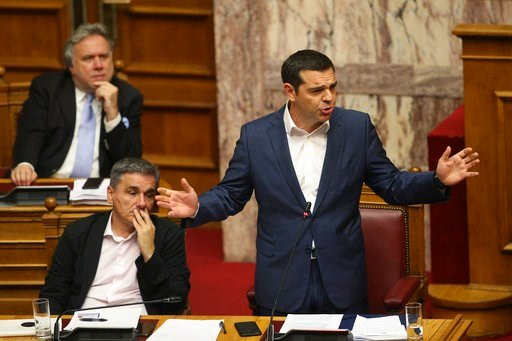 (AP Photo/Petros Giannakouris). Greek Prime Minister Alexis Tsipras, right, speaks next to Finance Minister Euclid Tsakalotos, during a parliamentary session ,in Athens, on Thursday, June 14, 2018. The head of Greece's main opposition party Kyriakos Mi...