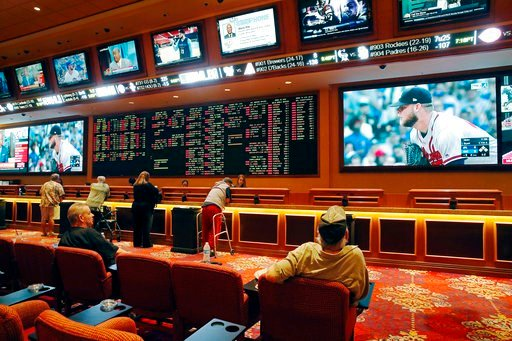 (AP Photo/John Locher, File). FILE – In this May 14, 2018, file photo, people make bets in the sports book at the South Point hotel and casino in Las Vegas. A day before New Jersey's governor makes his state's first legal wager on a sporting event, spo...