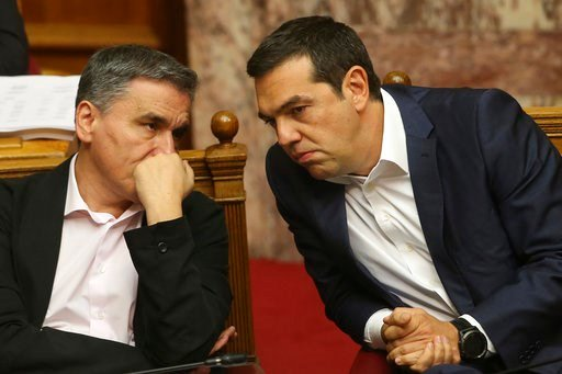 (AP Photo/Petros Giannakouris). Greek Prime Minister Alexis Tsipras, right, and Finance Minister Euclid Tsakalotos talk during a parliamentary session in Athens, on Thursday, June 14, 2018. The head of Greece's main opposition party Kyriakos Mitsotakis...
