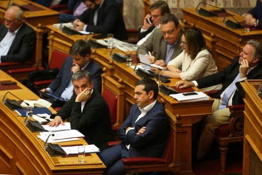 (AP Photo/Petros Giannakouris). Greek Prime Minister Alexis Tsipras, center, and Finance Minister Euclid Tsakalotos, third left, attend a parliamentary session in Athens, on Thursday, June 14, 2018. The head of Greece's main opposition party Kyriakos M...