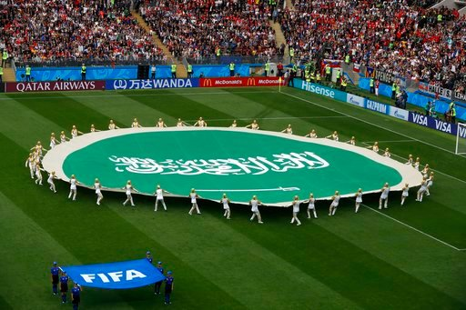 (AP Photo/Darko Bandic). Volunteers hold the flag of Saudi Arabia ahead of the group A match between Russia and Saudi Arabia which opens the 2018 soccer World Cup at the Luzhniki stadium in Moscow, Russia, Thursday, June 14, 2018.