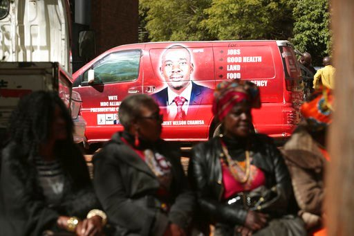 (AP Photo/Tsvangirayi Mukwazhi). Supporters of Zimbabwes main oppositon leader, Nelson Chamisa are seen close to his campaign vehicle outside the magistrates courts in Harare, Thursday, June, 14, 2018.Zimbabwes military backed president and a youthful ...