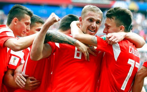 (AP Photo/Matthias Schrader). Russia's Yuri Gazinsky celebrates with teammates after scoring his side's first goal during the group A match between Russia and Saudi Arabia which opens the 2018 soccer World Cup at the Luzhniki stadium in Moscow, Russia,...
